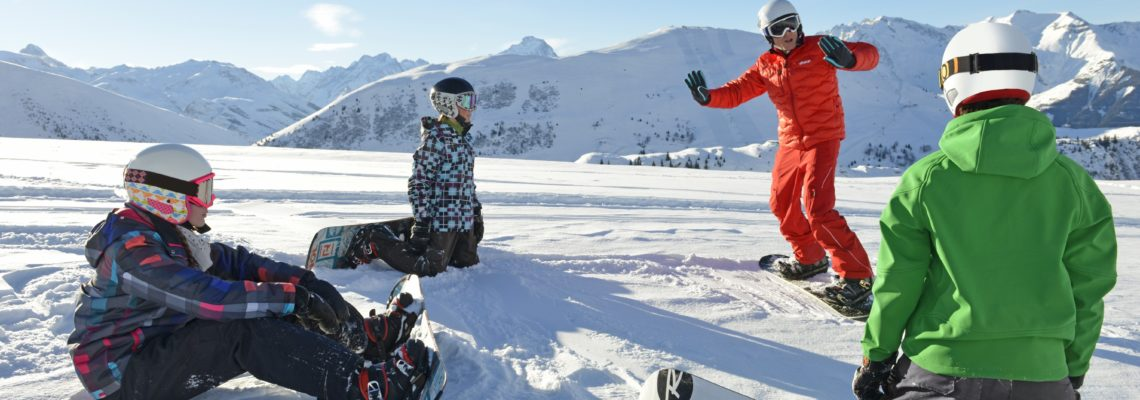 Ski Instructor giving snow boarders a lesson on the snow