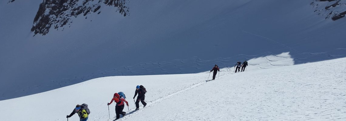 Cross country skiers in a line across a snow slope