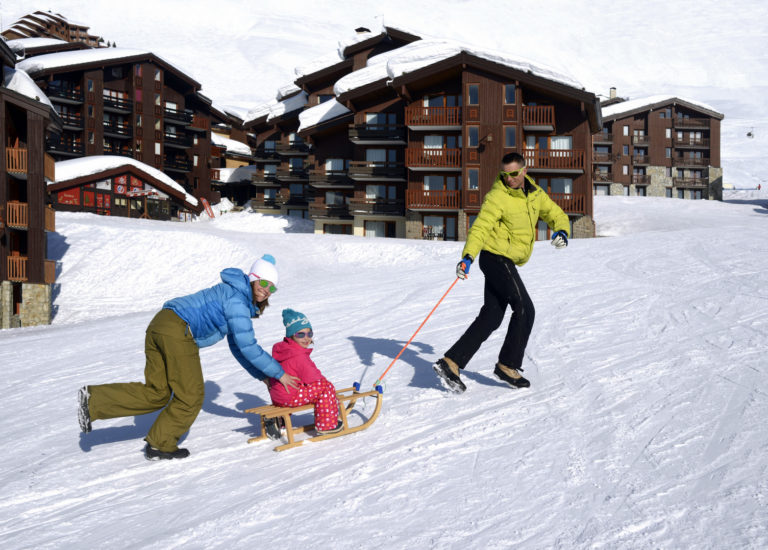 Child on sled on snow with parents in La Plagne Ski Resort, France