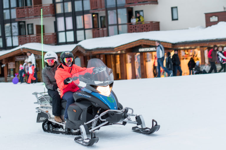 Two people on a snowmobile on snow in Val Thorens