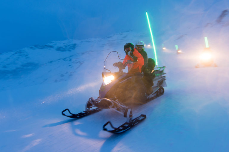 Two people on a snowmobile at night in snow in Val Thorens