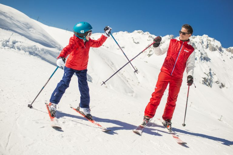 Student and ski instructor high fiving with ski poles