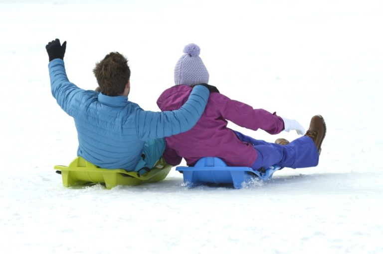 Two people on bum boards going down a snow slope