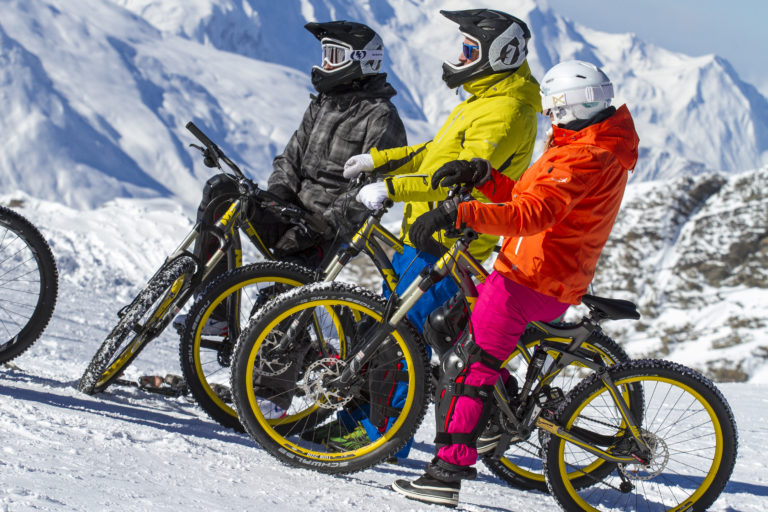 Three mountain bikers on snow at Val Thorens, France