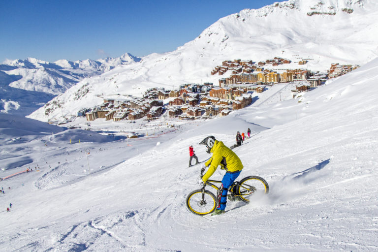 Mountain biker going down a snowy slope in Val Thorens, France