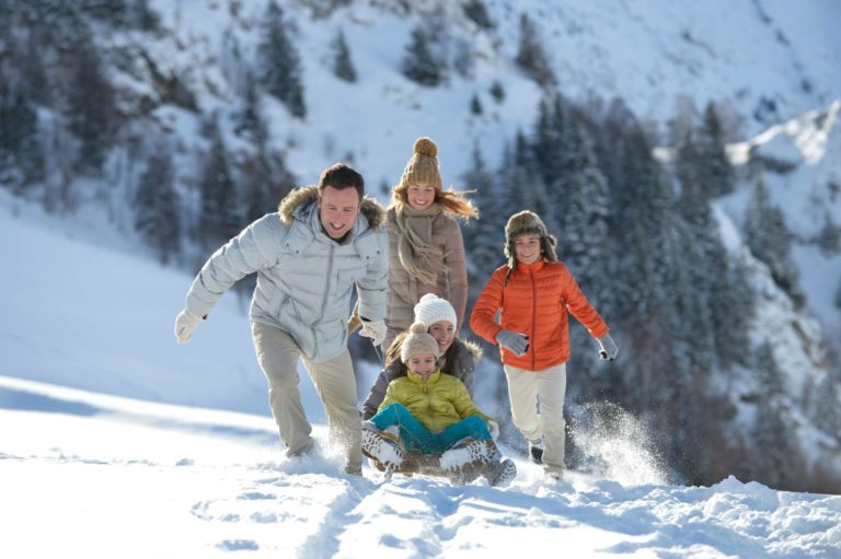 Family playing in the snow with a sled at Val Morel Club Med