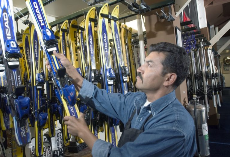 Man getting skis at Ski equipment hire and rental shop