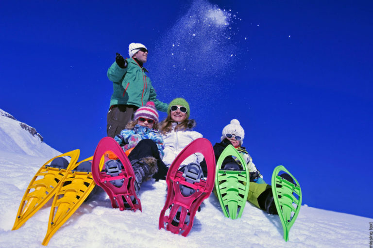 Friends in snow shoes sitting in the snow at Val d'Isere, France