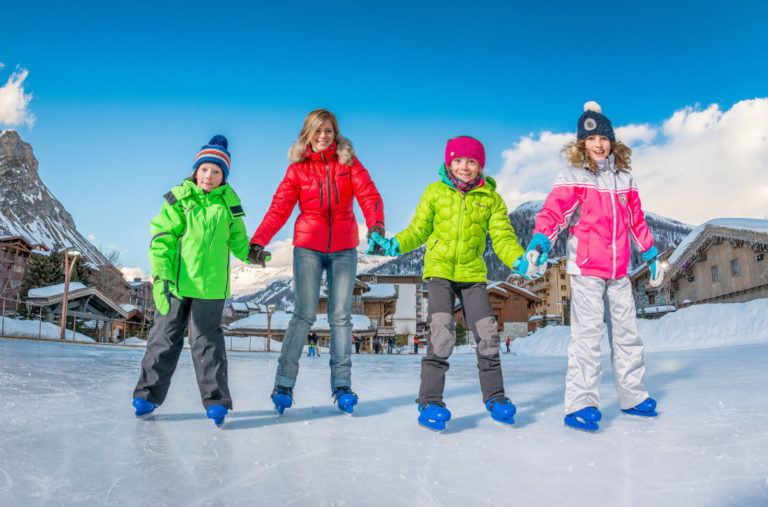 Family ice skating on an ice rink in Val d'Isere Ski Resort, France