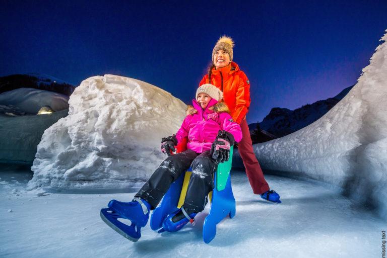 Two girls ice skating in Val d'Isere Ski Resort, France