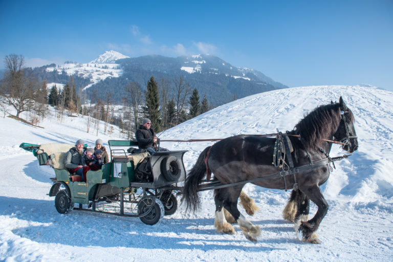 Family in horse draw cart in th snow in Kitzbuhel or Kitzbühel, Village, Austria