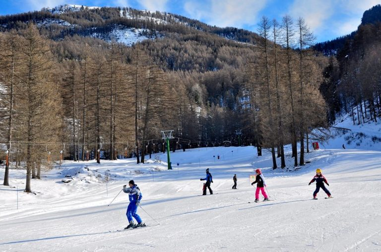 Alpine skiers on learners slope in Pragelato Vialattea Italy
