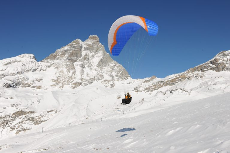 Para-skiing over snow covered mountain in Cervinia, Italy