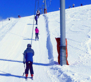Skiers being dragged up the slope on button lift
