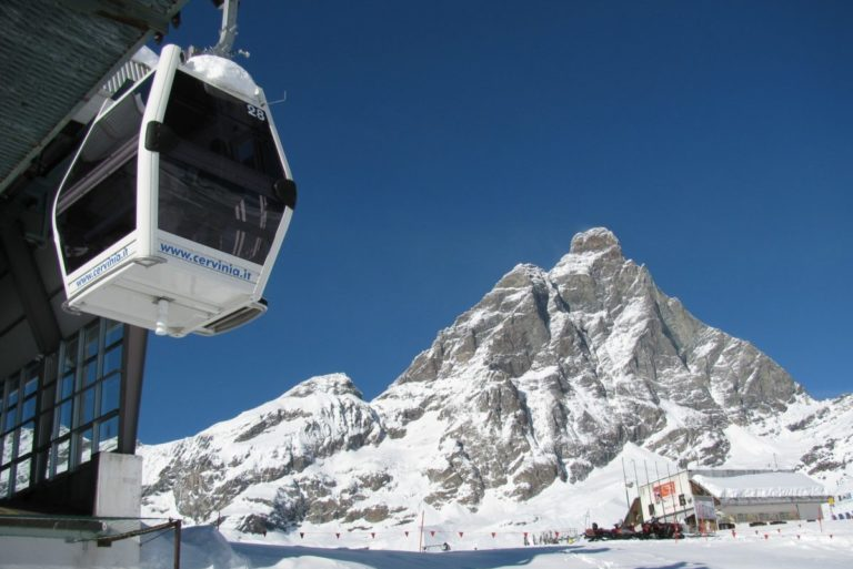 Gondola cable car going up snow covered mountain in Cervinia, Italy