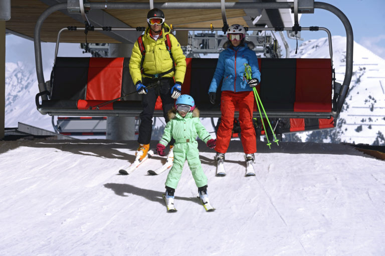 Family on chair lift in La Plagne Ski Resort, France