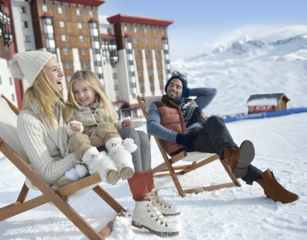 Family sitting on deck chairs on snow in La plagne