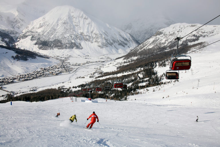 Alpine skiers and chair lifts on snow in Livigno Ski Resort, Italy