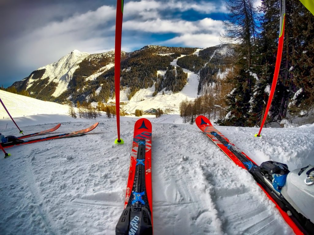 Red alpine skis and poles at the top of a steep piste