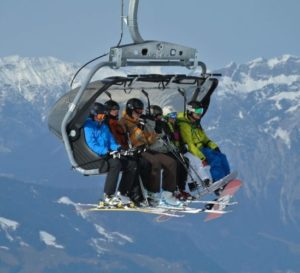 Four skiers in the air on a on a chair lift