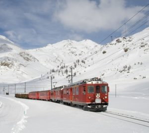 Red train in snow going to mountain top